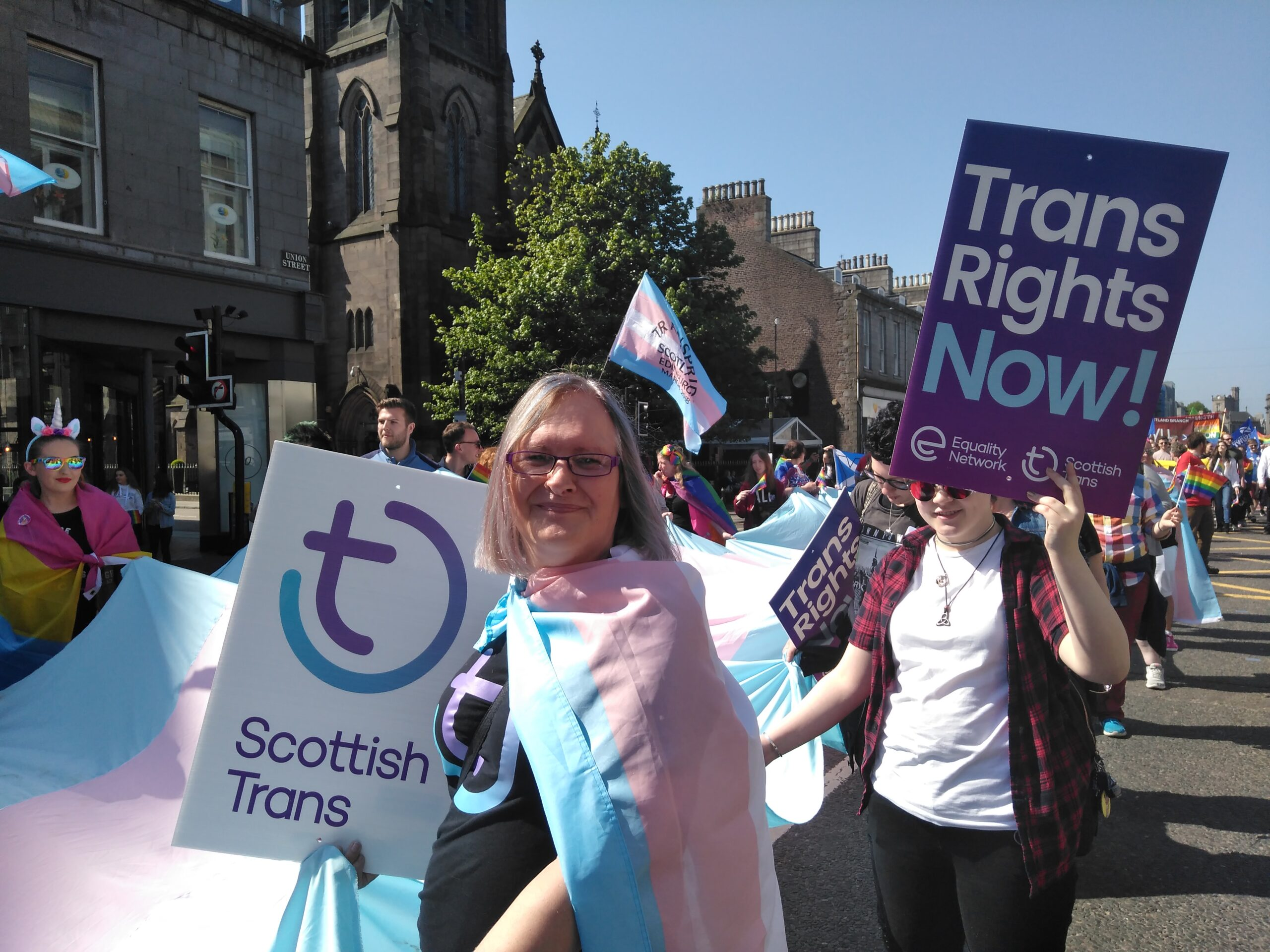 Scottish Trans large trans flag and placards on Pride march.