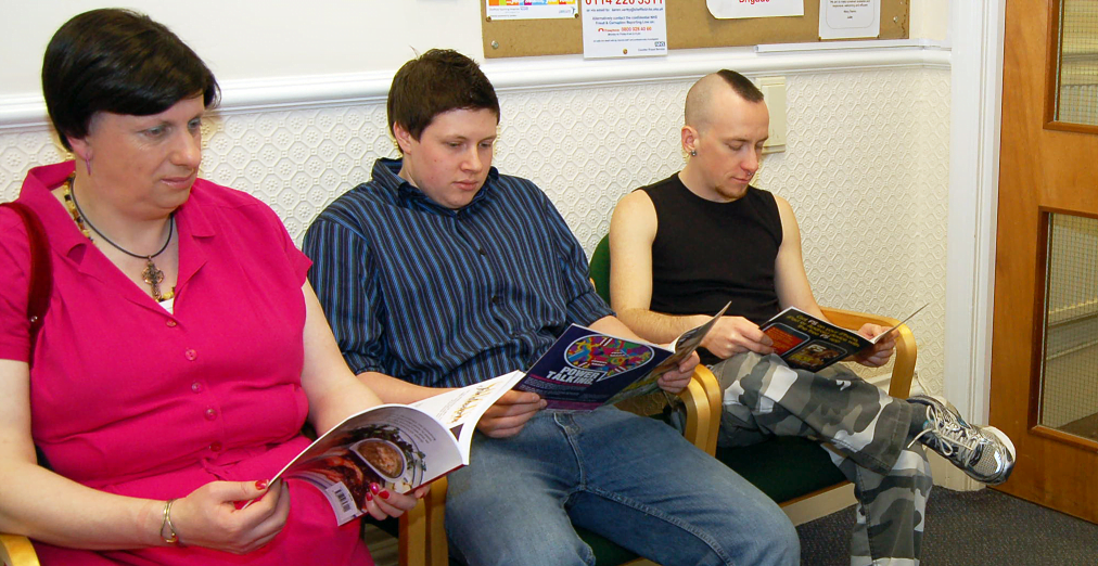 Trans people sitting in an NHS waiting room.