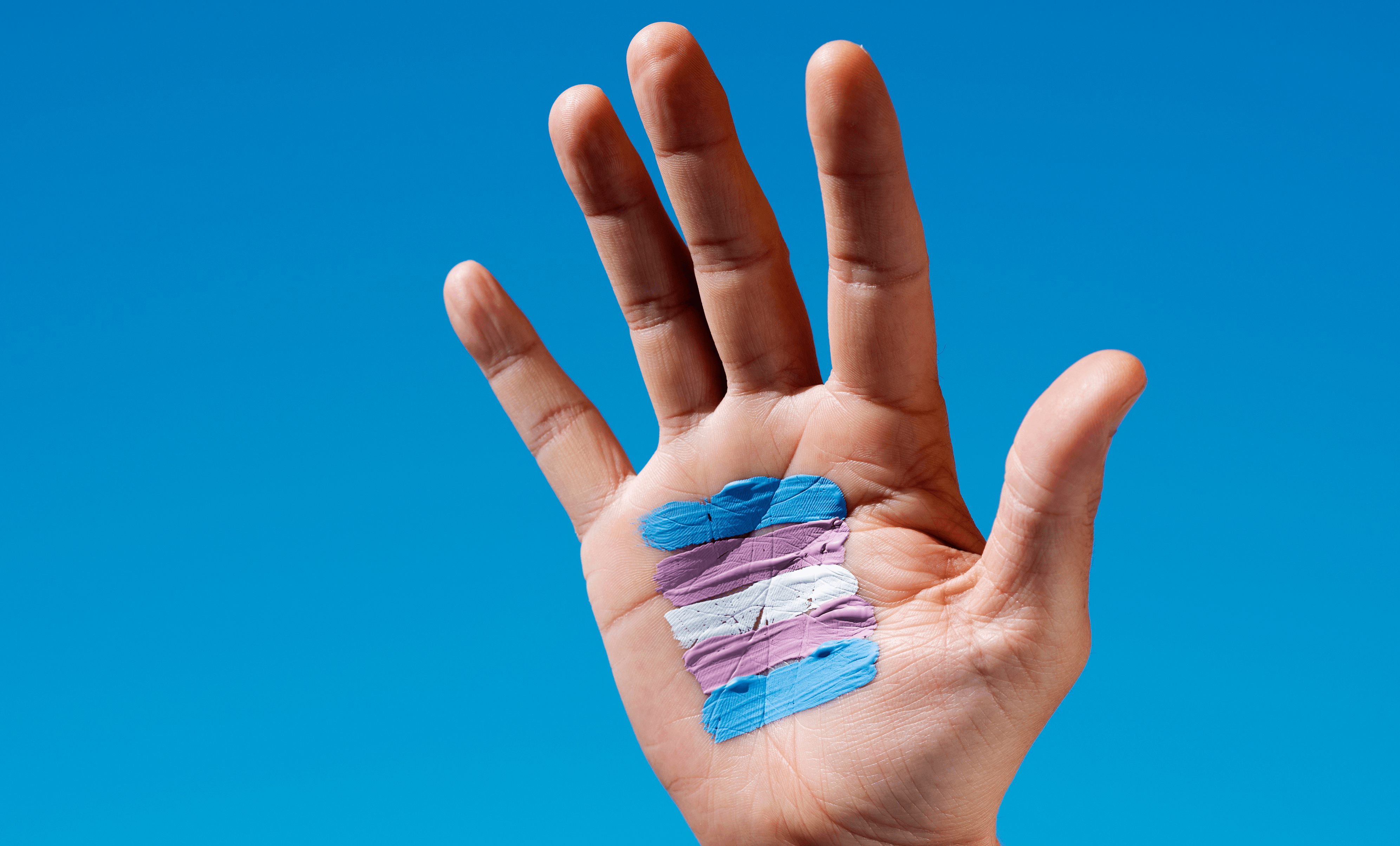 Photo of a hand raised up for help with a trans flag painted on its palm.